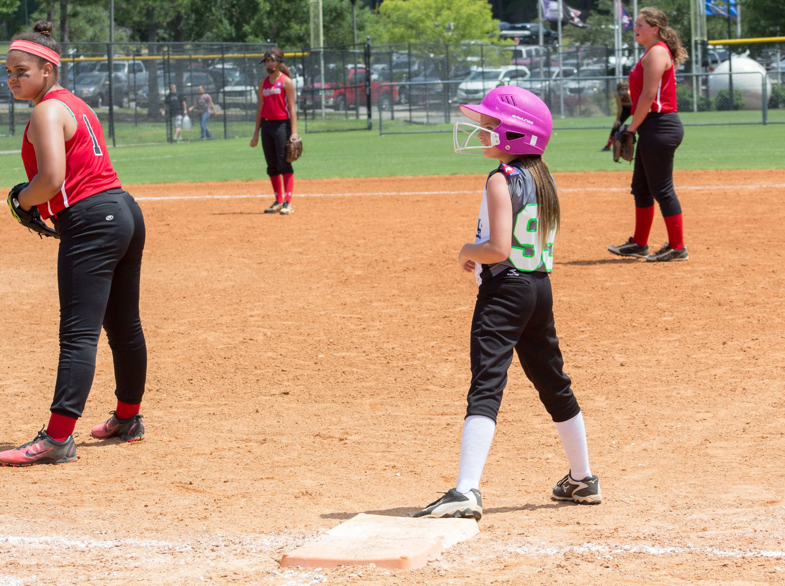 Image of girl on first base playing softball.