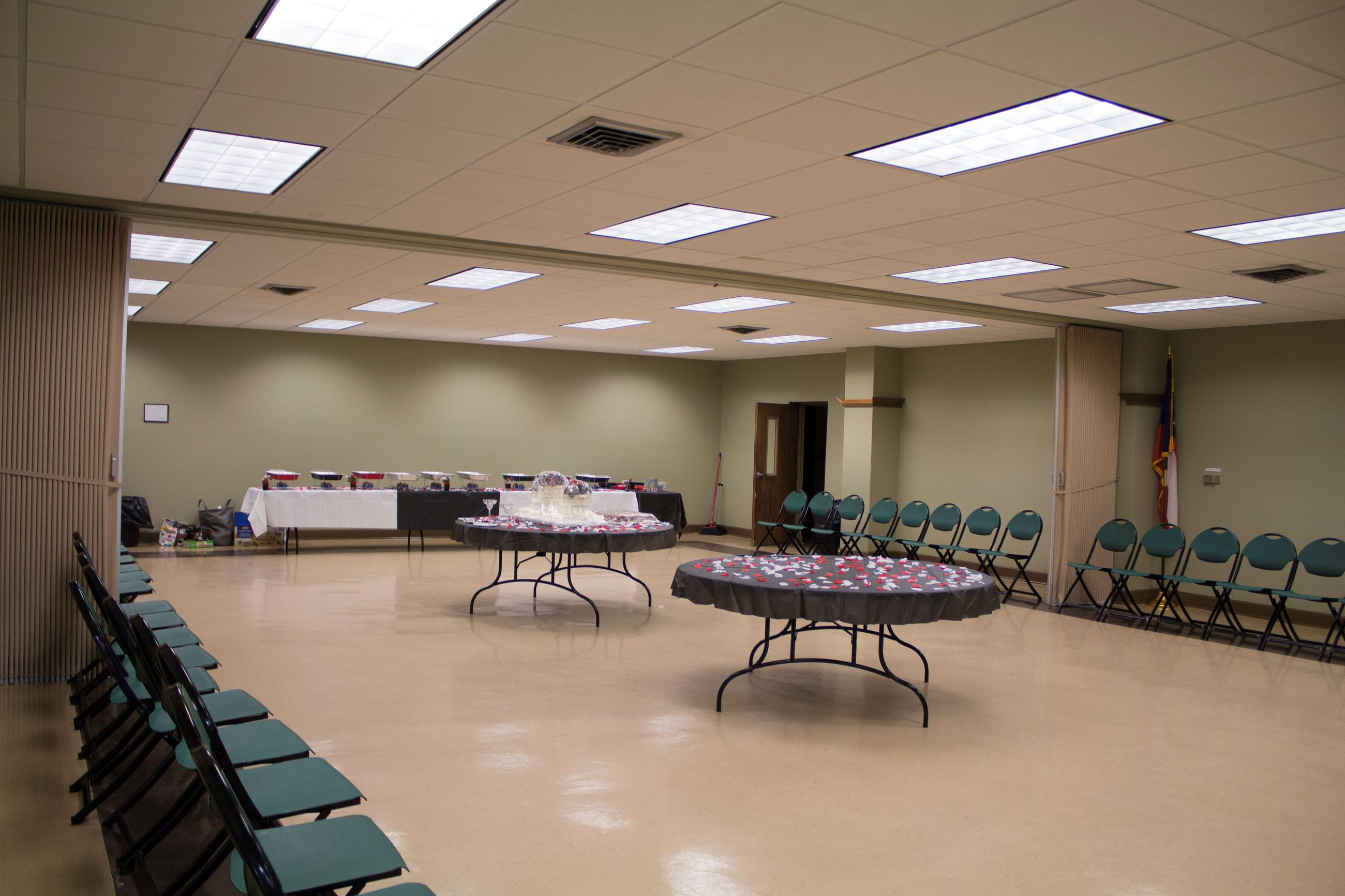 An image of a multipurpose room with tables and chairs set up for a community event.