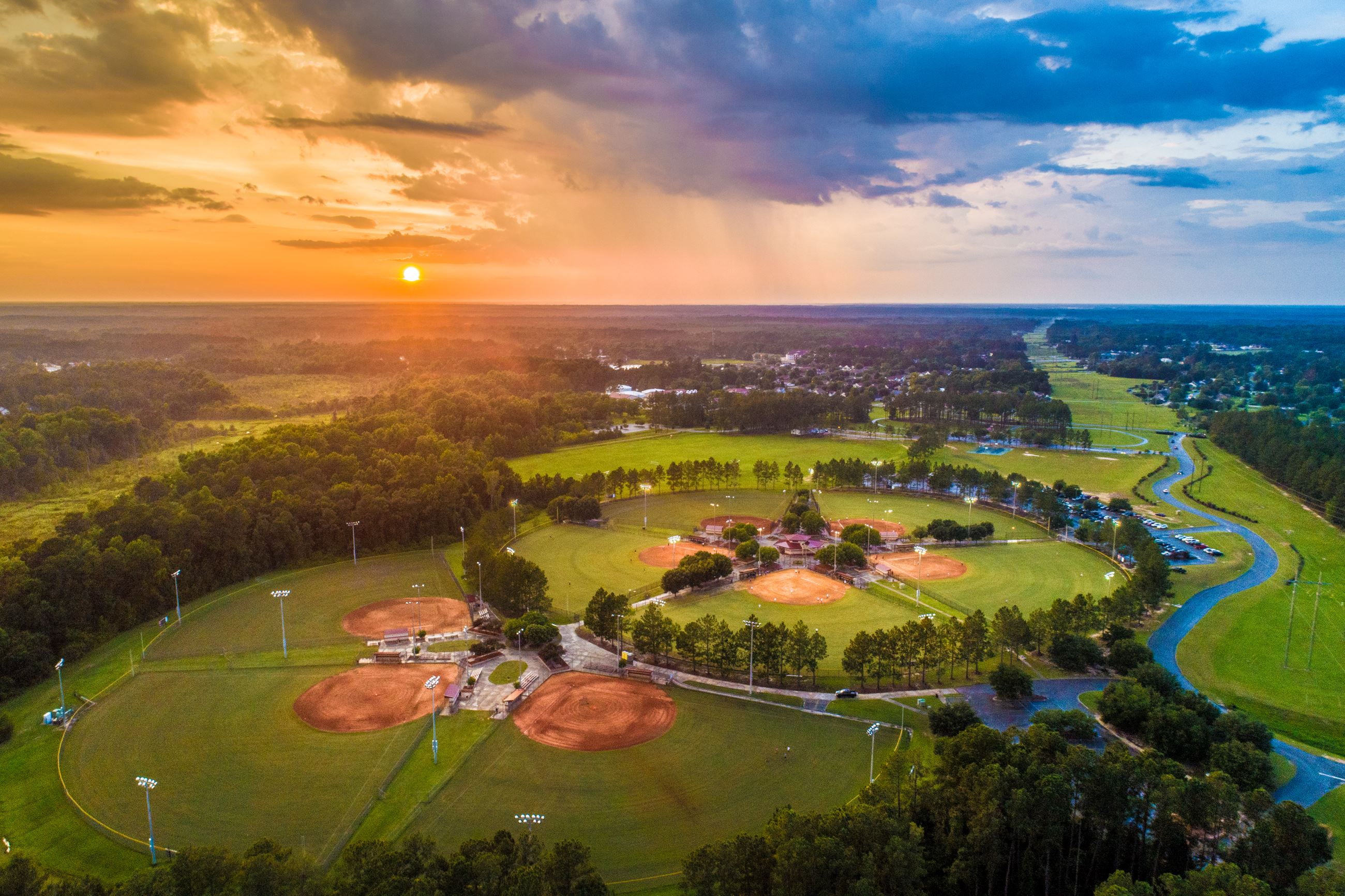 An image of an aerial view of baseball fields at sunset.