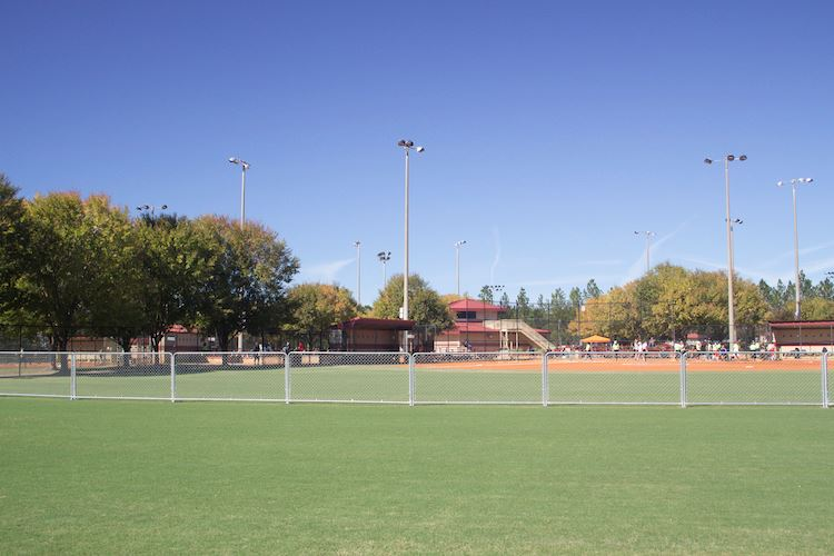 An image of an outfield of a baseball field look toward home plate with temporary fencing.