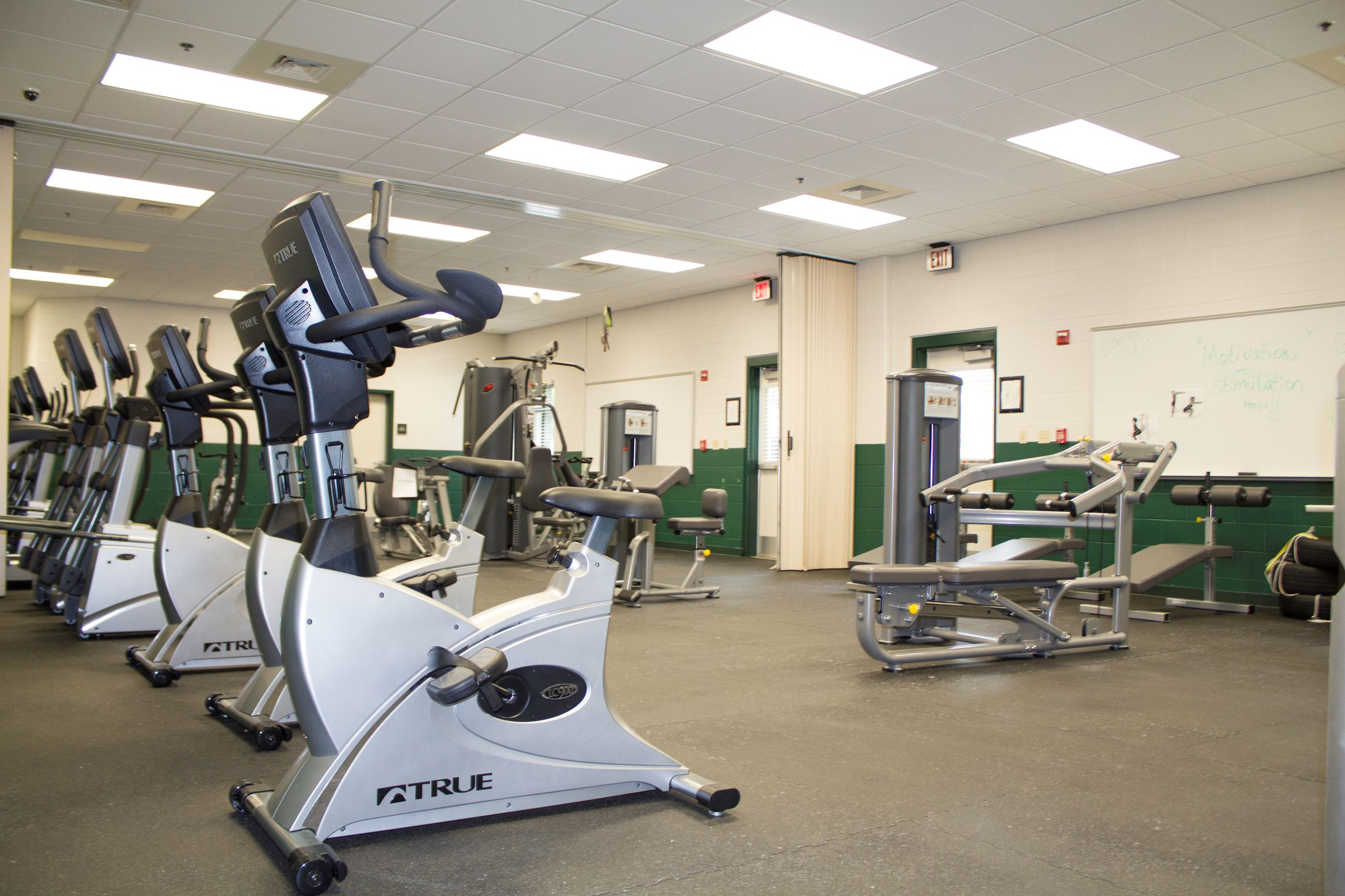 An image of a workout room with stationary bicycles and weightlifting equipment.