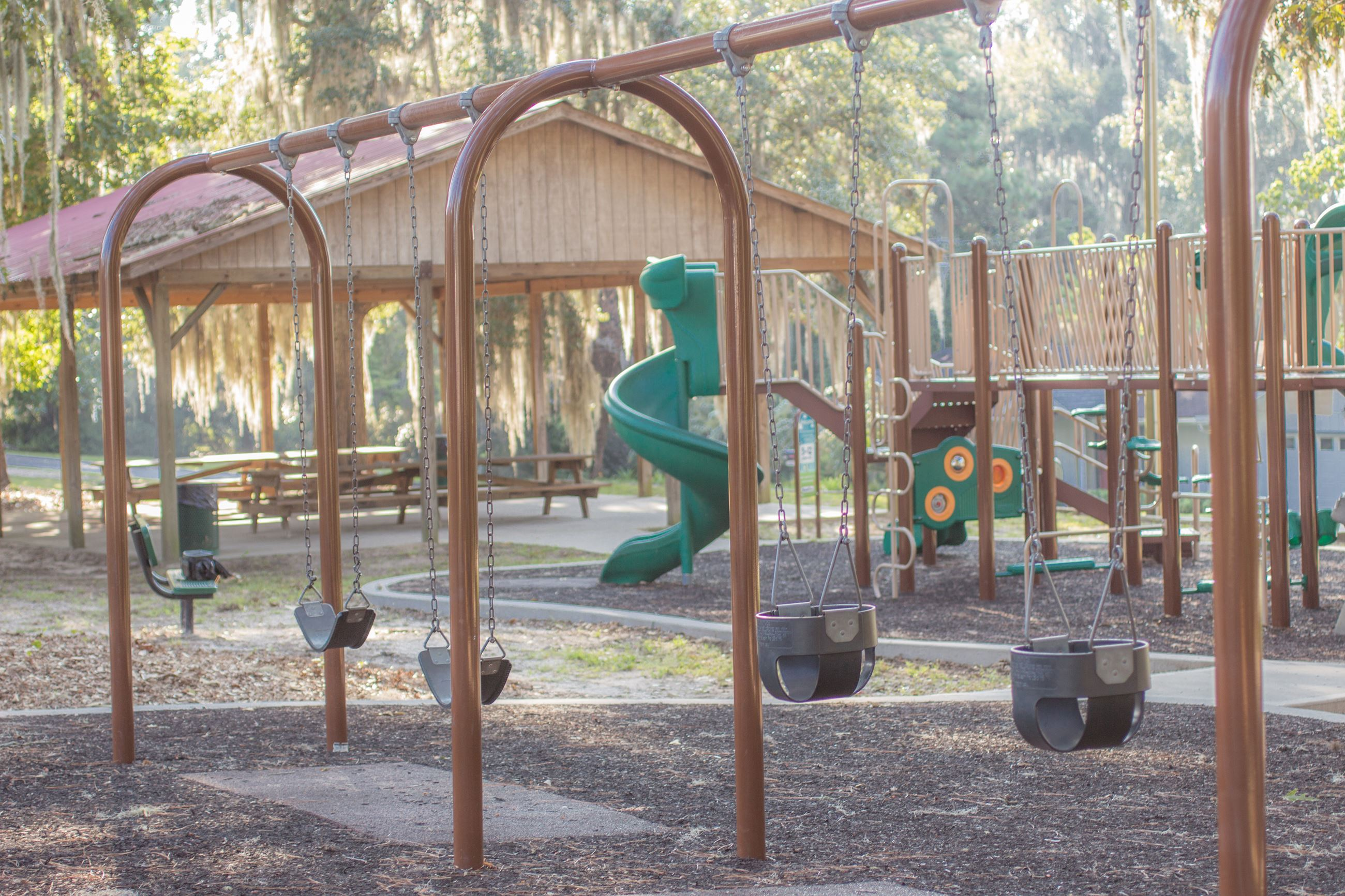 An image of a swing set in front of a playground.