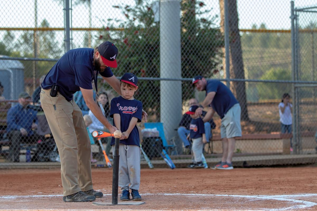An image of a coach helping a young baseball player with his bat.
