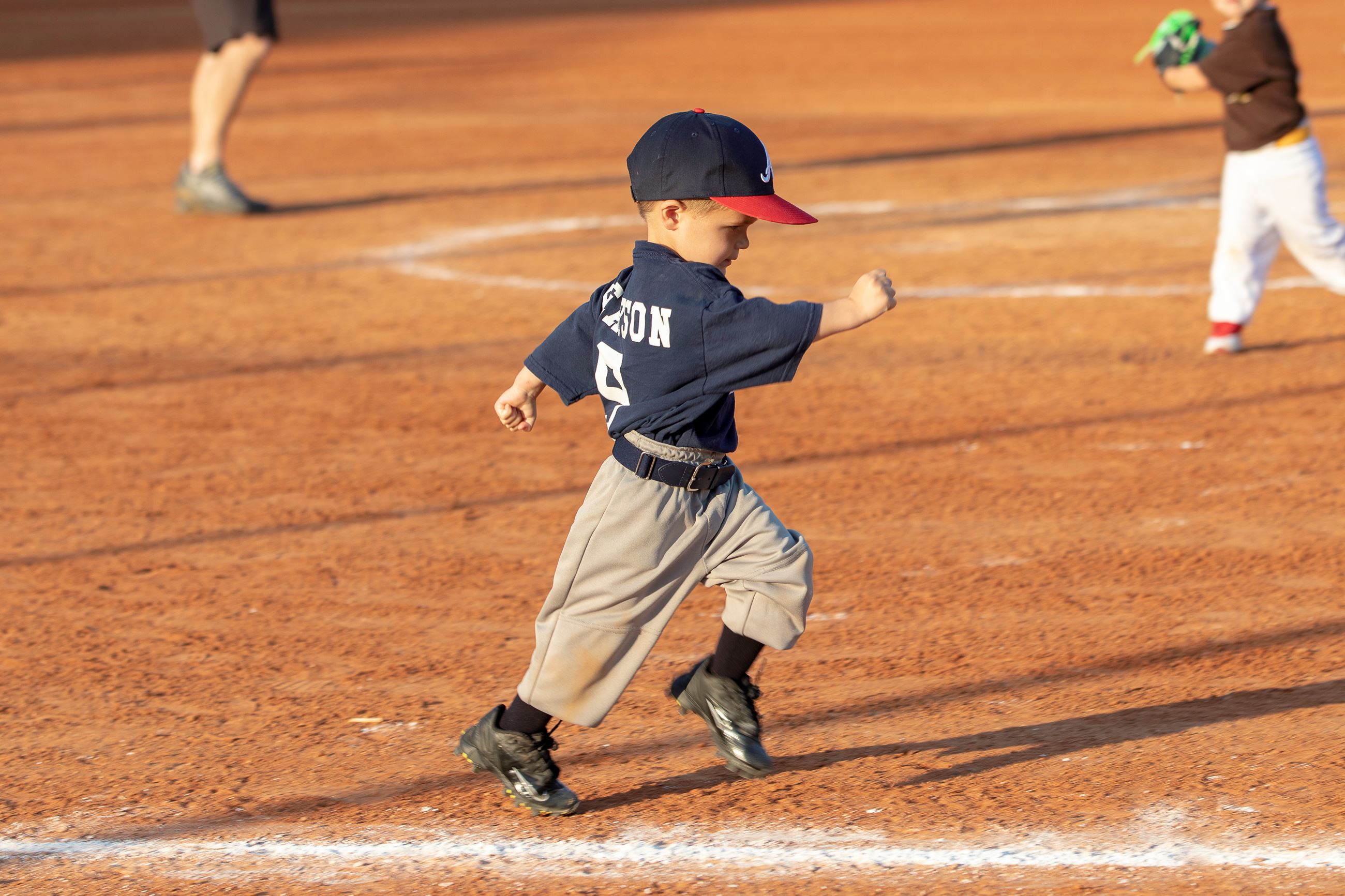 Image of little boy running to first base.