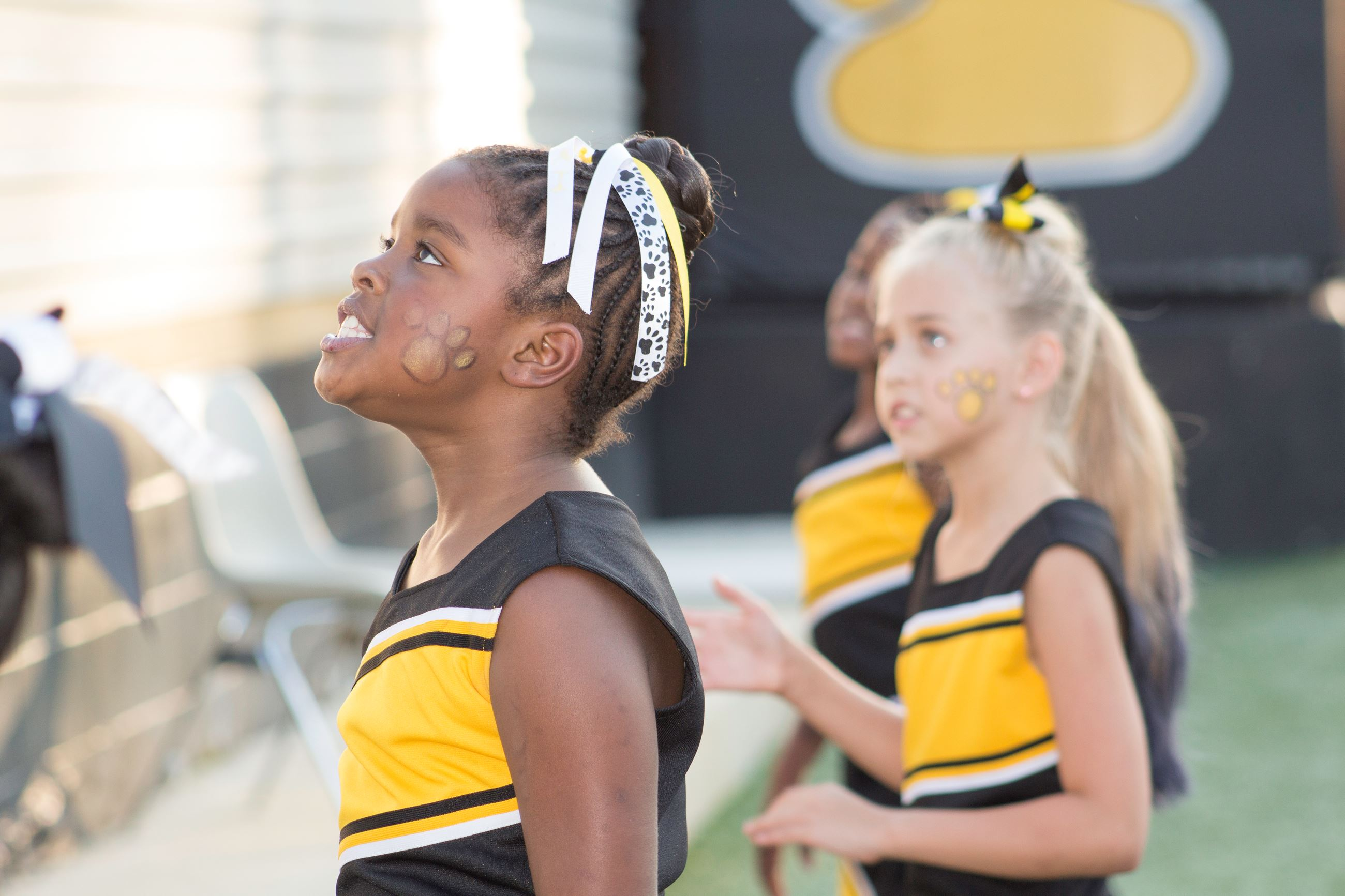 Image of little girls cheering on football sideline.