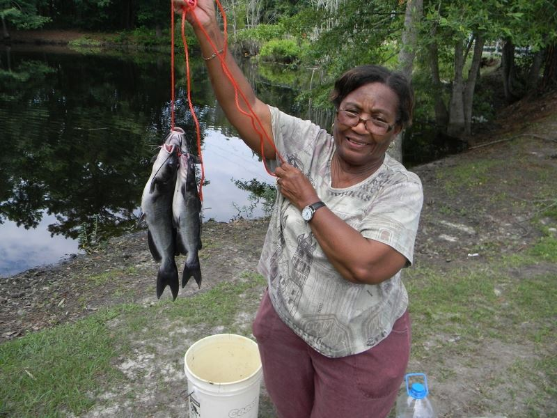 Woman poses with two dead fish