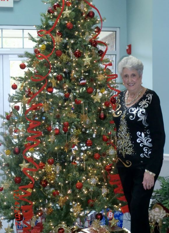 Woman poses in front of christmas tree