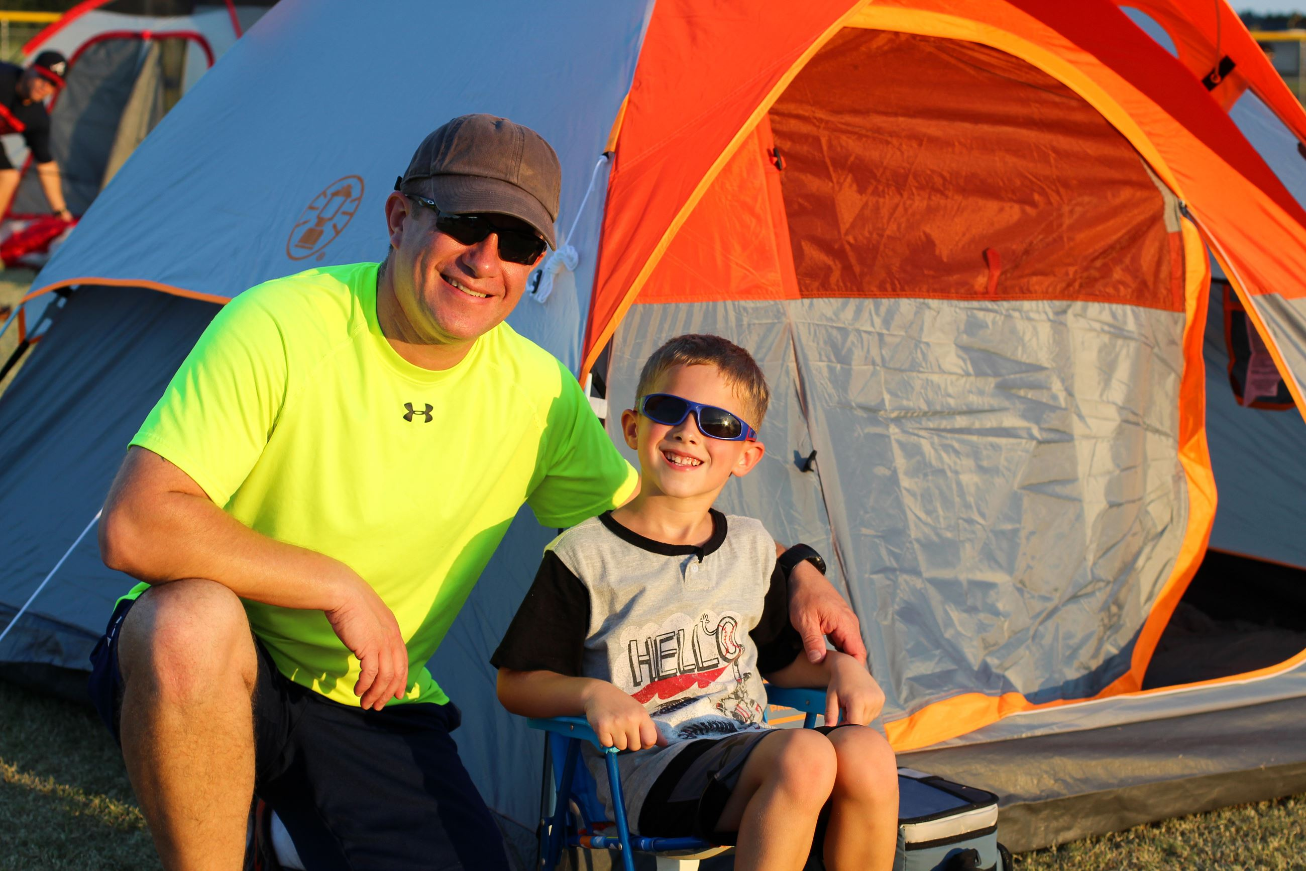 Image of father and son smiling in front of tent.