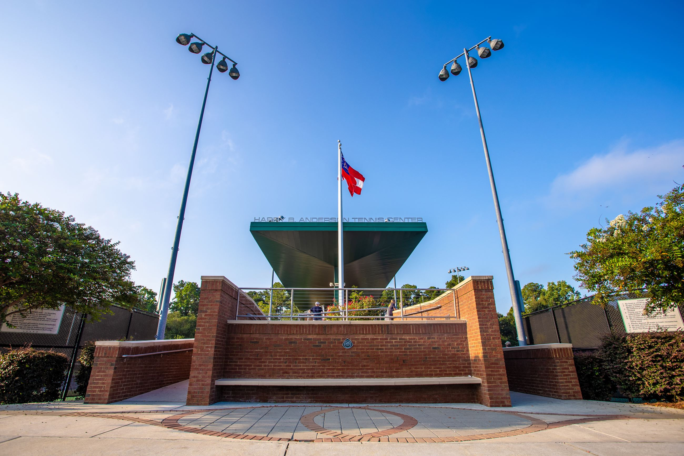 An image of the front entrance of a tennis center with a brick wall and an American flag.