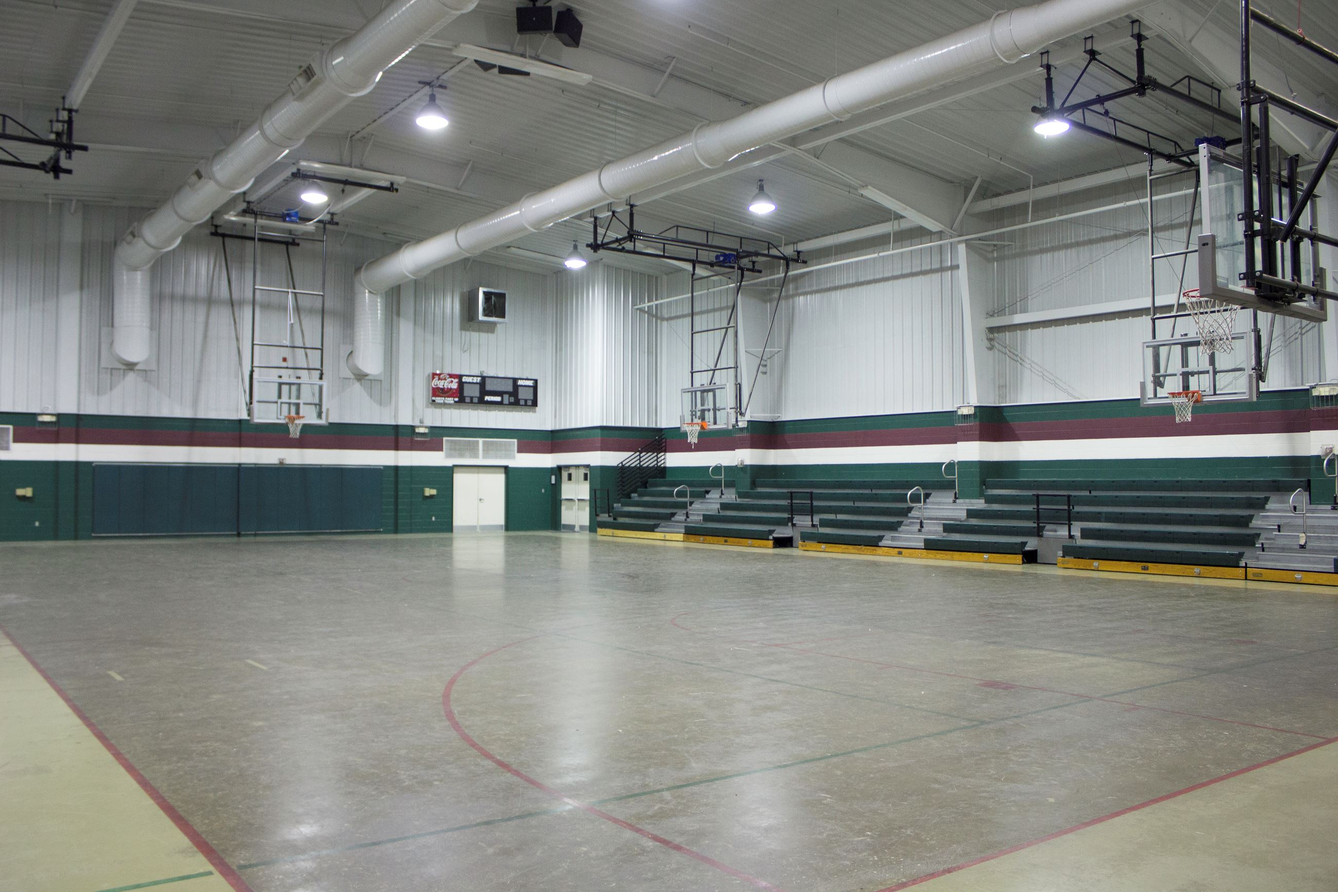 An image of a gymnasium with a full size basketball court and bleachers.