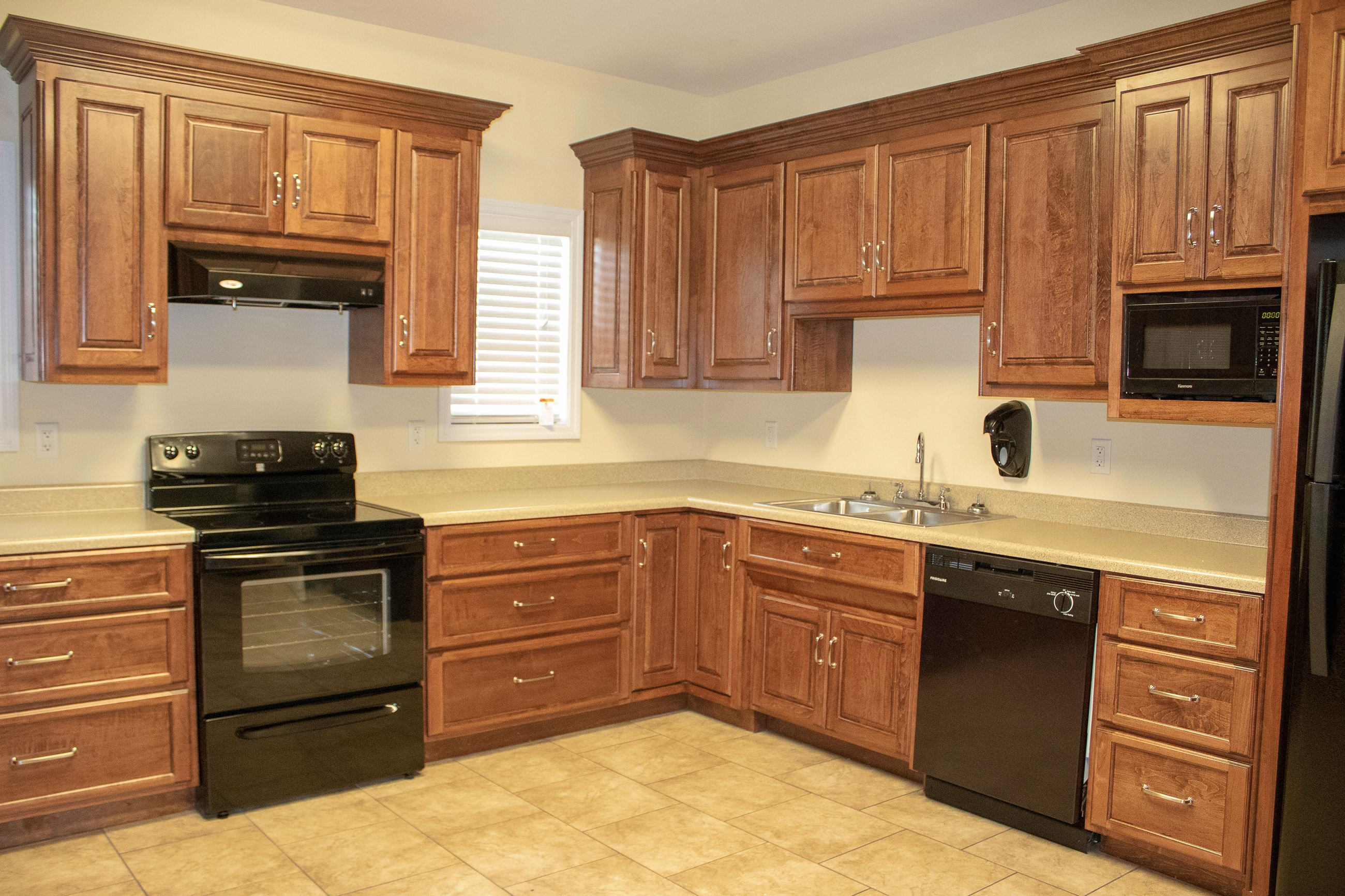 An image of the kitchen inside the Naylor Community Center with oak cabinets.