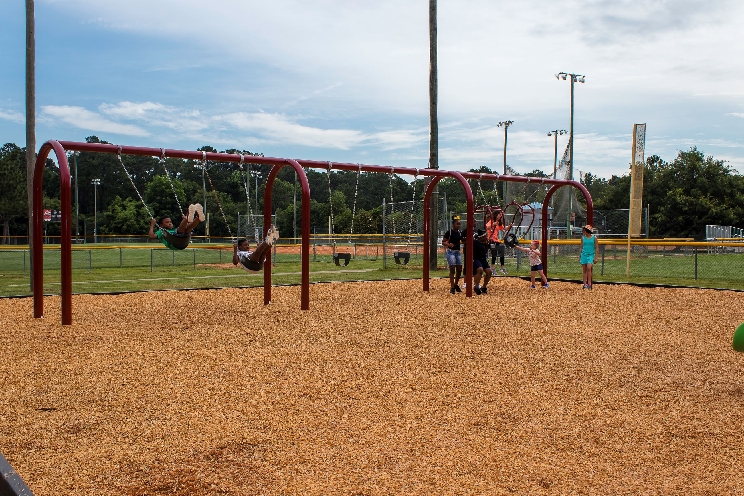 An image of a large swing set with children swinging.