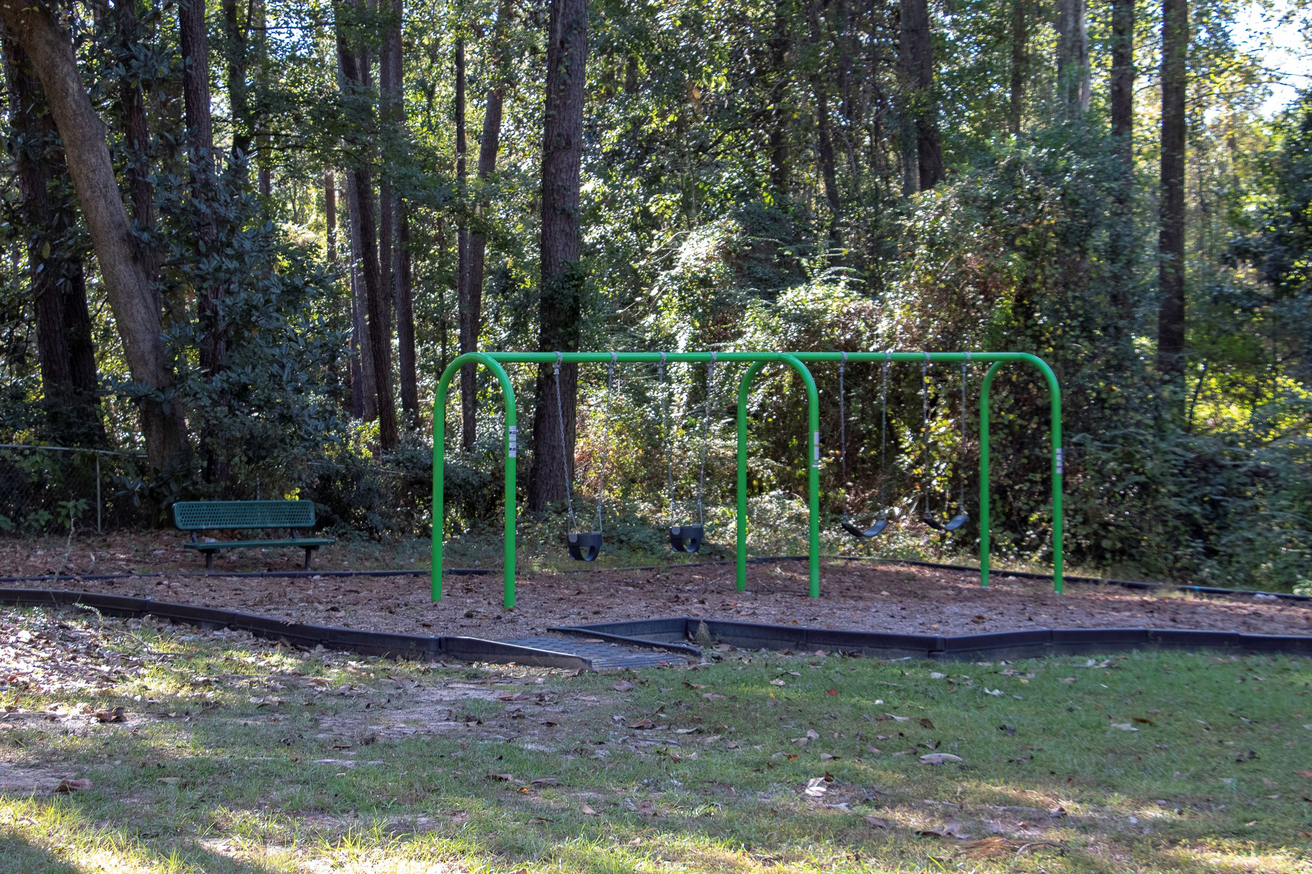 An image of swing sets in a shaded park.