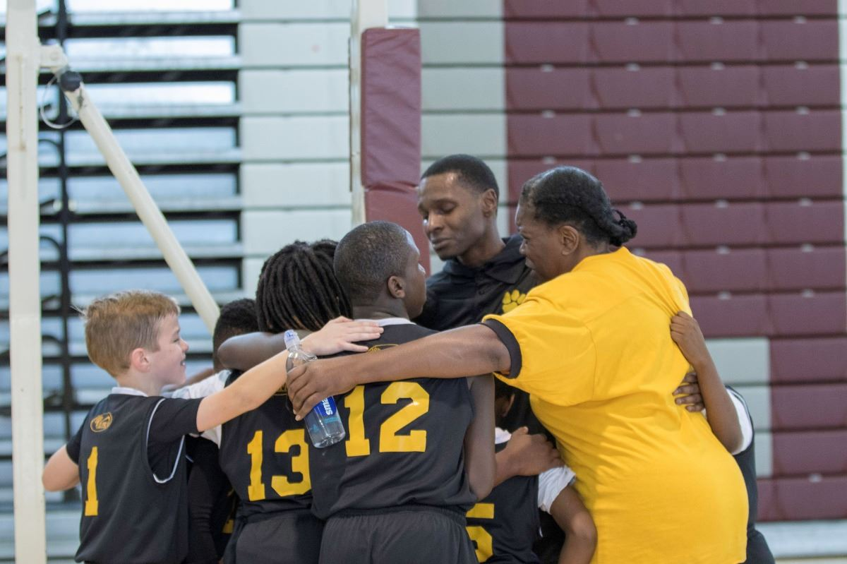 An image of a basketball team in a group hug.