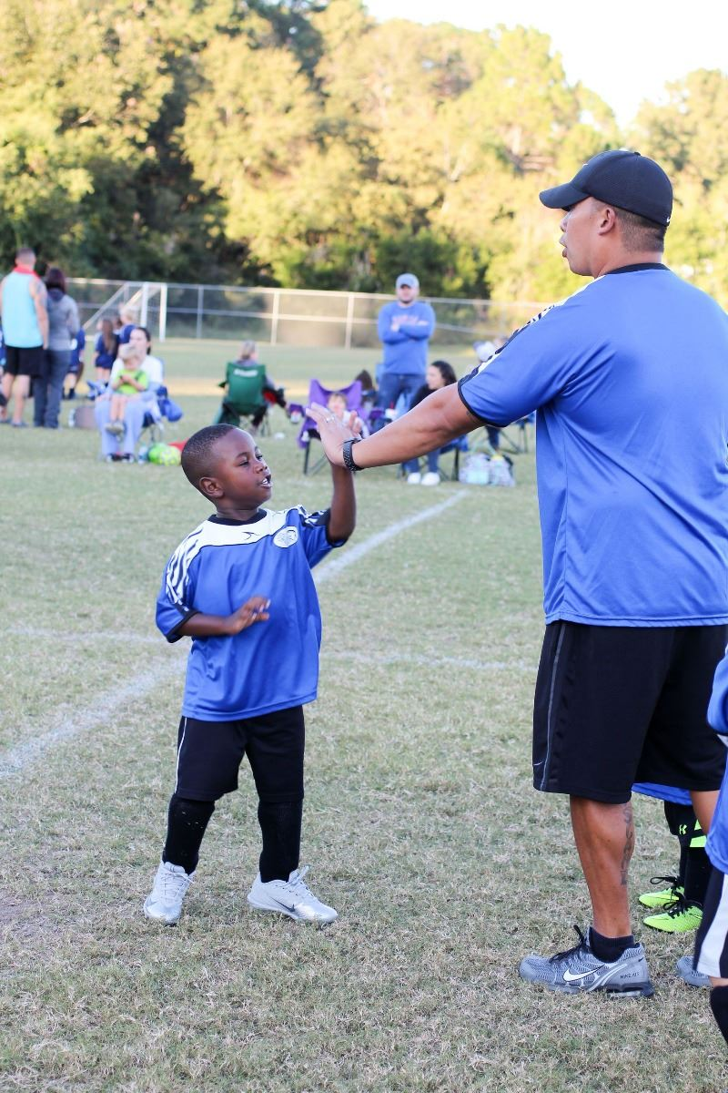 An image of a soccer coach giving a high five.