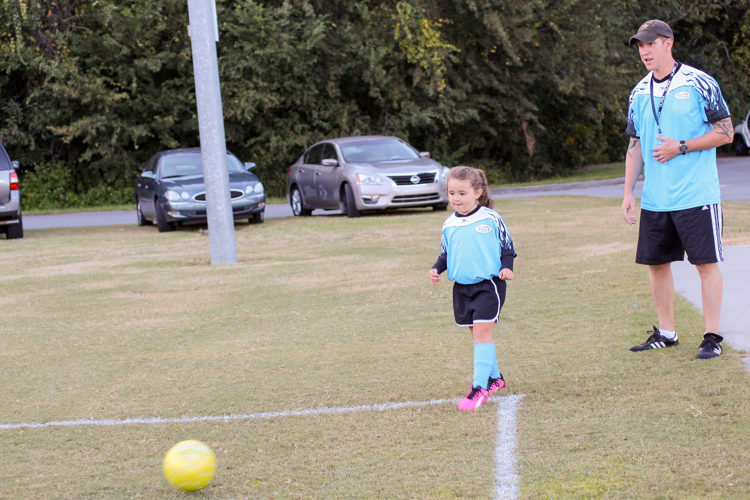 Image of girl kicking a soccer ball.