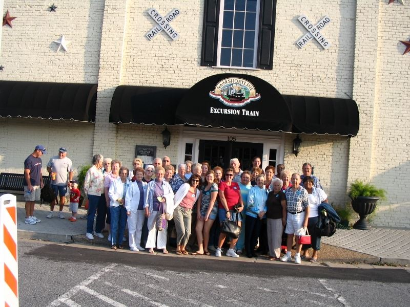 Large group poses outside of tavern