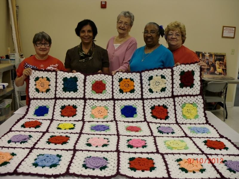 Women pose with a quilt