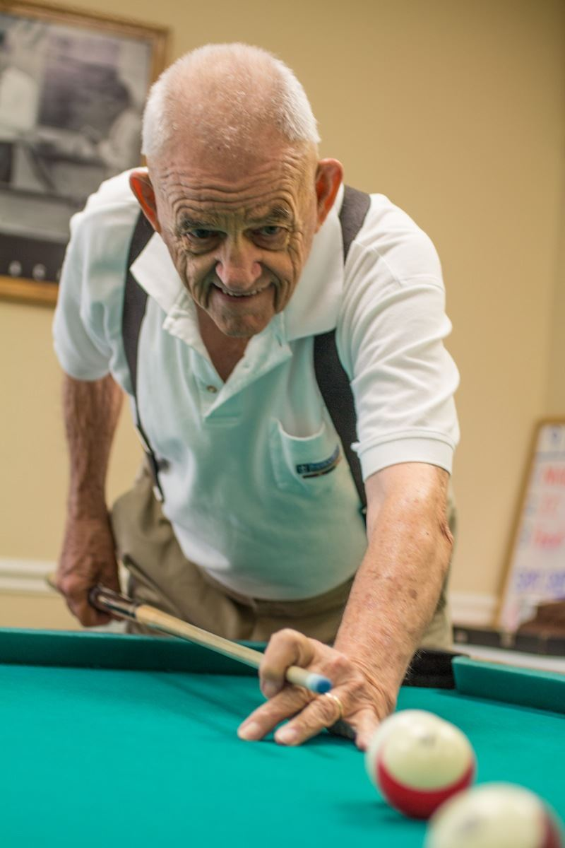 Senior citizen plays pool